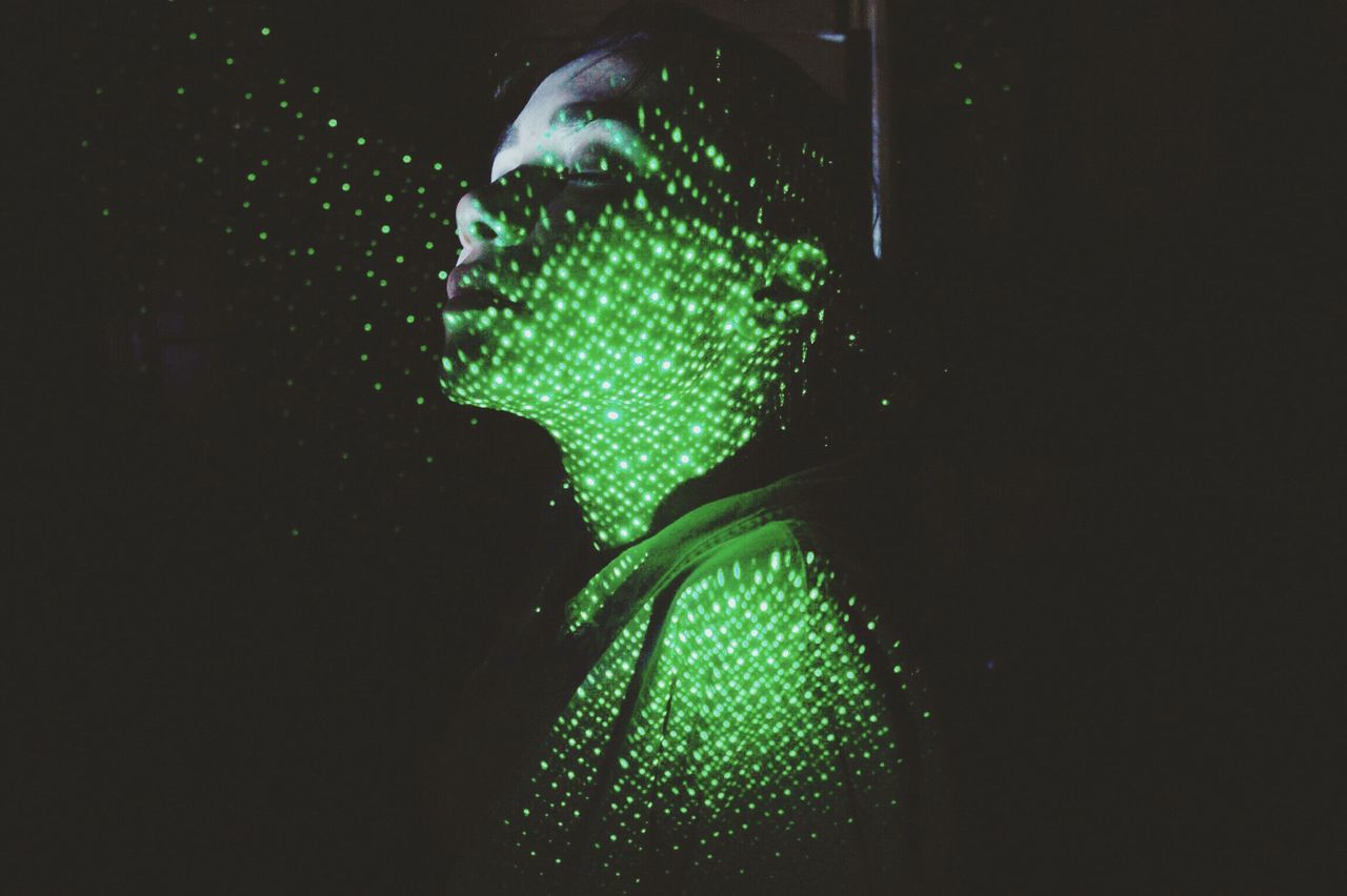 Close-up of shirtless woman with illuminated green lights against black background