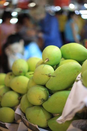 Close-up of raw mangoes at market stall