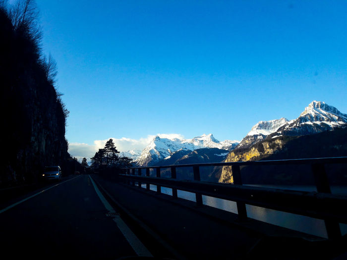 Road by snowcapped mountains against clear blue sky