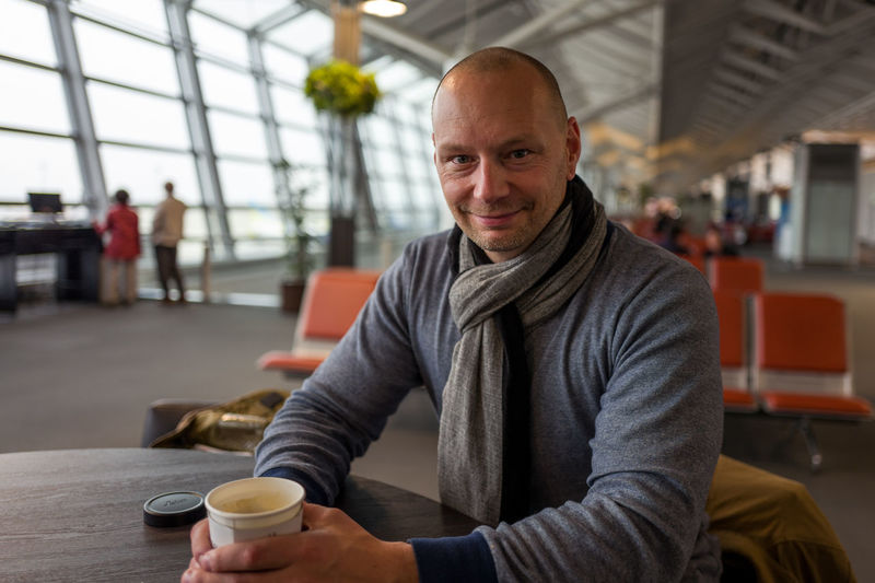 Portrait of smiling man holding disposable coffee cup while sitting at chubu centrair international airport