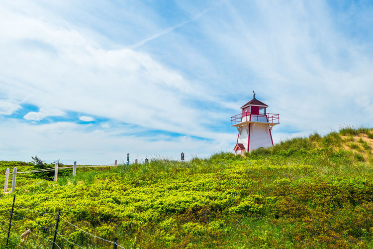 Lighthouse Architecture Beauty In Nature Building Building Exterior Built Structure Canada Tourist Attractions Cloud - Sky Coverheads Day Environment Field Grass Green Color Growth Land Landscape Nature No People Outdoors Plant Prince Edward Island Sky Tower Tranquility