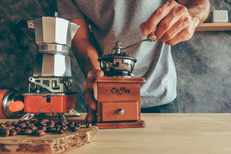 Midsection of man making coffee at table