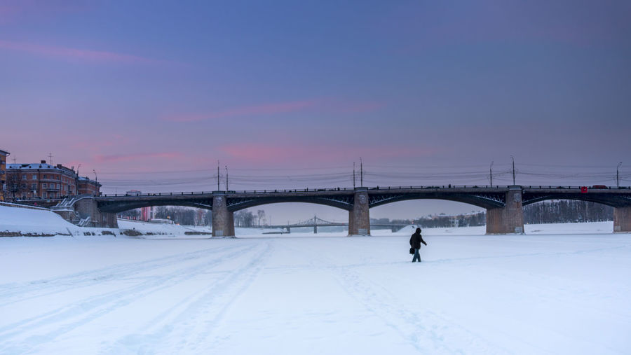 Man with a briefcase crosses the frozen Volga river on foot just a few meters away from a stone bridge. Sky Connection Bridge Bridge - Man Made Structure Cold Temperature Snow Winter One Person Real People City Sunset Engineering Travel Destinations Travel Path Not Taken Determination Space For Text Space For Copy Copy Space Russian Winter