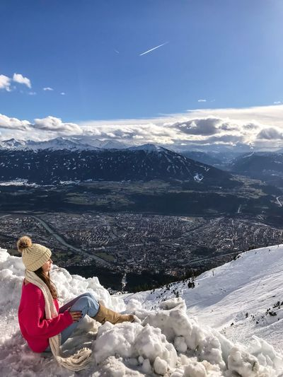Side view of woman sitting on snow at mountain peak against sky