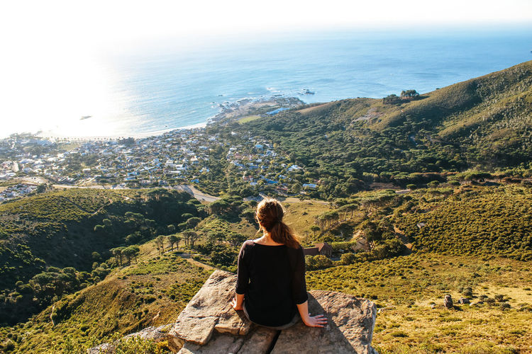 Woman sitting on the edge of a cliff at Kloof Corner in theTable mountain National Park enjoying the view of camps bay in Cape Town Sitting One Person Rear View Looking At View Young Adult Mountain Water Tranquility Relaxation Casual Clothing Tranquil Scene Outdoors Sea Nature Cliff Kloof Corner Camps Bay Cape Town South Africa Ridge Corner Edge View Point Hiking Trekking