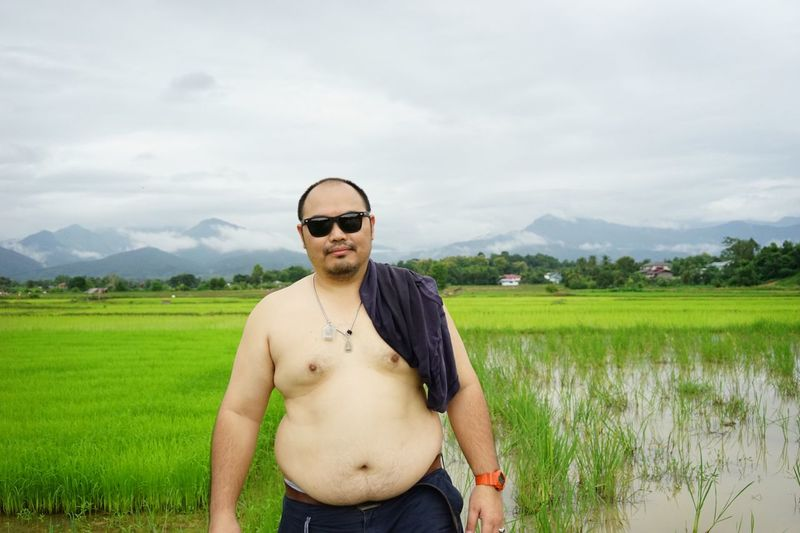 Portrait of shirtless man standing on field