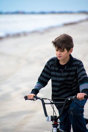 Young man riding bicycle on beach