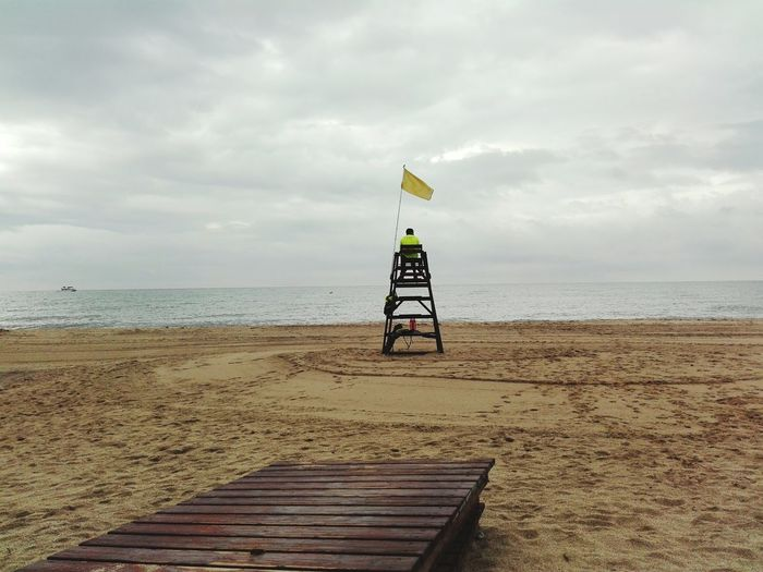 Rear view of man sitting on lifeguard chair at beach against cloudy sky