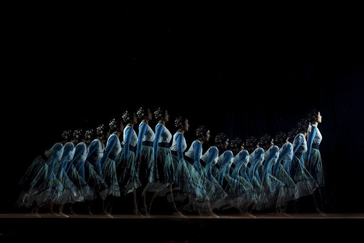 Multiple image of woman dancing against black background