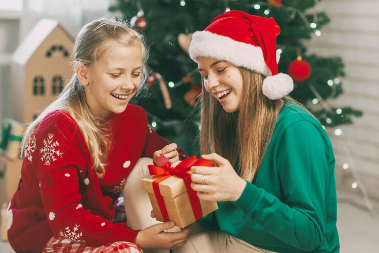 Two happy and beautiful teenage girls in new year's outfits open gifts at home