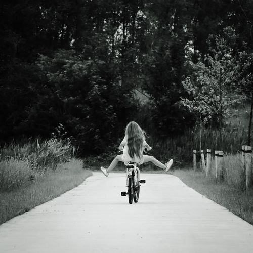 Rear view of girl riding bicycle on footpath