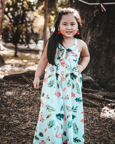 Portrait of smiling girl standing in forest