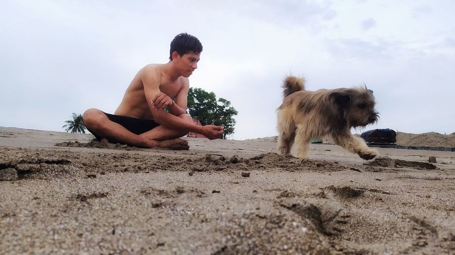 Full length of shirtless man with dog against sky
