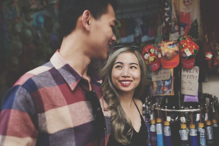 Portrait Of Smiling Young Couple Standing Against Store