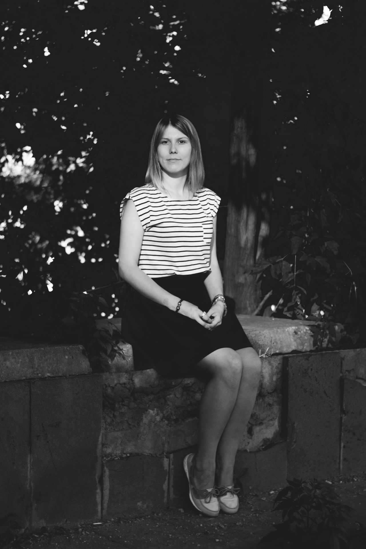 Full length portrait of young woman sitting on retaining wall against trees