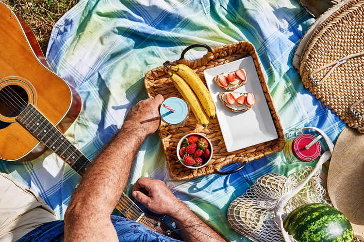 Summertime healthy picnic. fresh tropical fruit, sweet stawberry sandwiches and refreshing drink