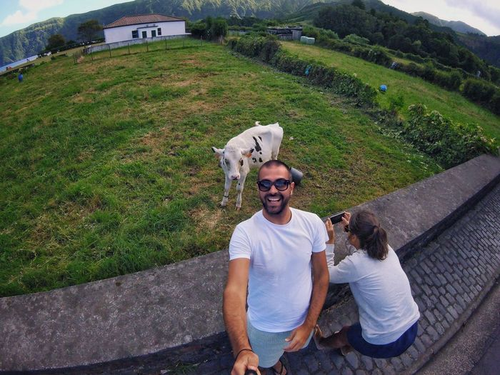 High angle view of happy man by woman photographing cow on field