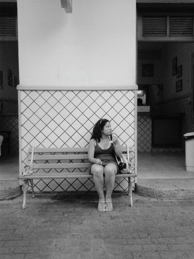 Full length of woman with ice cream sitting on park bench