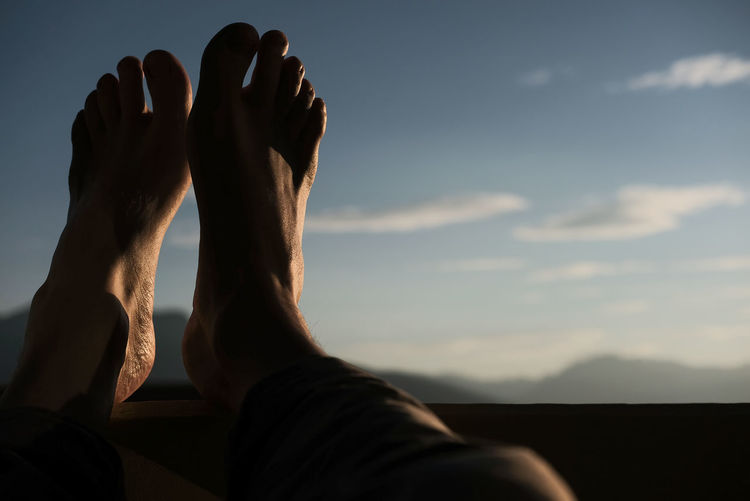 Low section of man with feet up against sky
