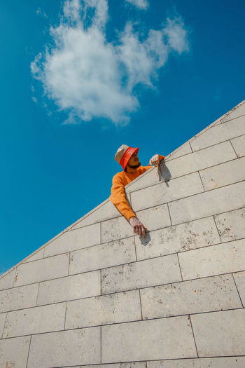 Low angle view of man standing by retaining wall against blue sky