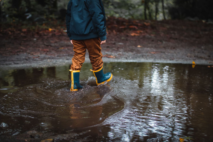 Low section of boy wearing boots while walking in puddle in forest