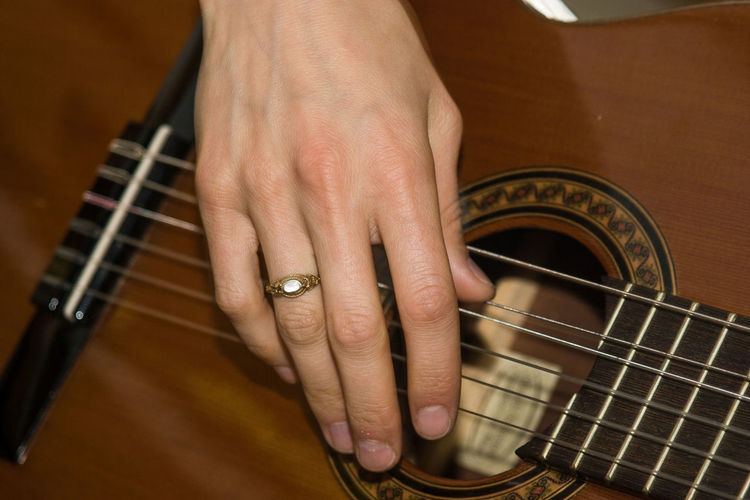 Cropped image of woman playing acoustic guitar