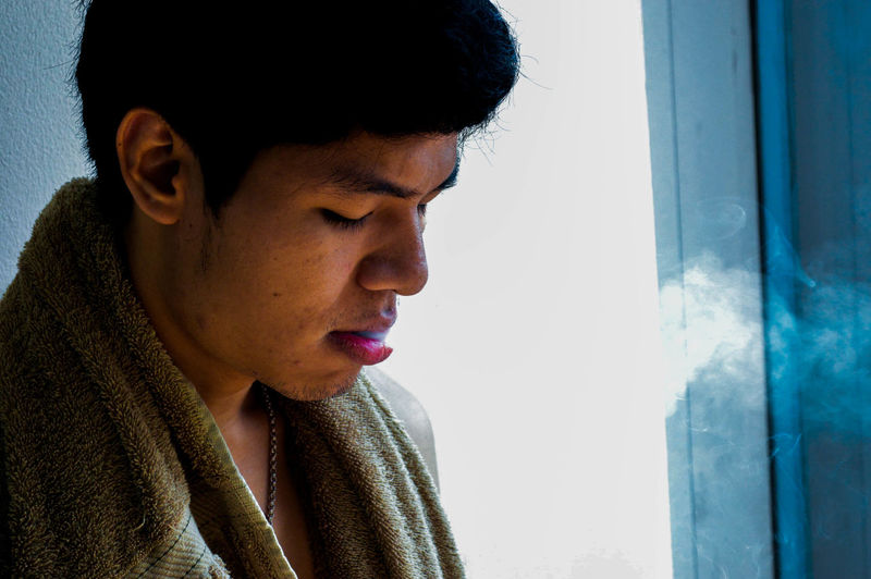 Close-up of man exhaling smoke at home