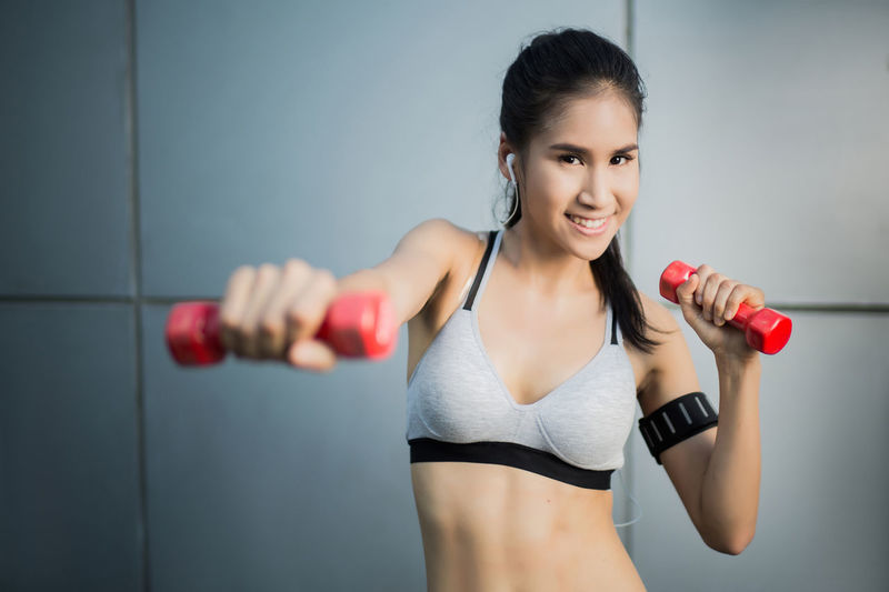 Adult Beautiful Woman Body Conscious Clothing Dumbbell Exercising Front View Gym Healthy Lifestyle Indoors  Lifestyles Muscular Build One Person Smiling Sport Sports Clothing Sports Training Strength Vitality Weight Weight Training  Women Young Adult Young Women