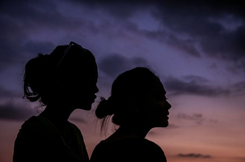 Silhouette friends against cloudy sky during sunset