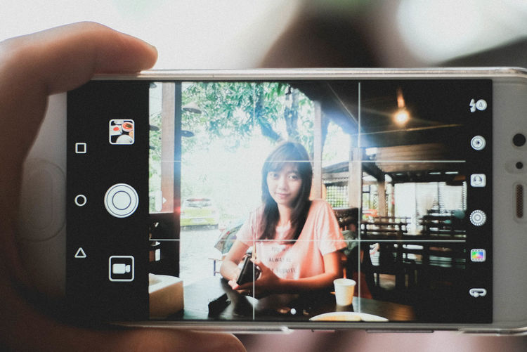 Portrait of smiling woman photographing through smart phone