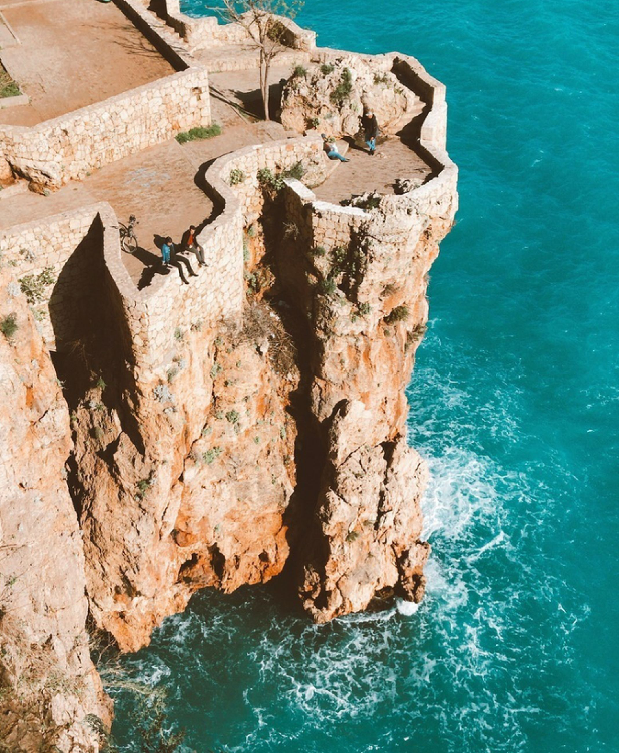 water, rock, sea, solid, rock - object, nature, rock formation, high angle view, day, animal wildlife, sunlight, animal, animal themes, animals in the wild, outdoors, cliff, no people, land, blue, turquoise colored