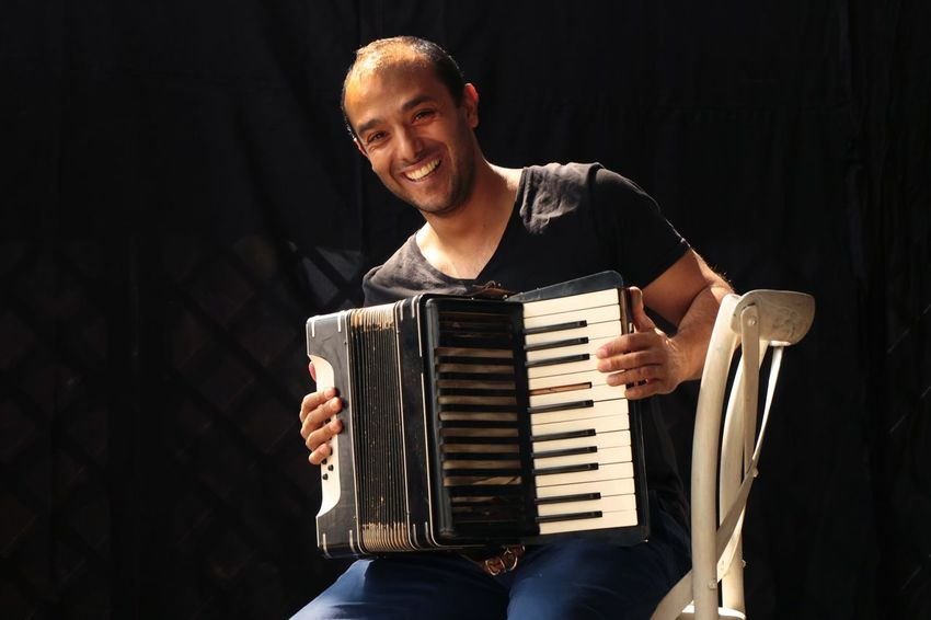 Musician Music Musical Instrument One Person Front View Arts Culture And Entertainment Musician Accordion Artist Young Adult Indoors  Men Real People Musical Equipment Leisure Activity Playing Three Quarter Length Casual Clothing Black Background Performance Lifestyles