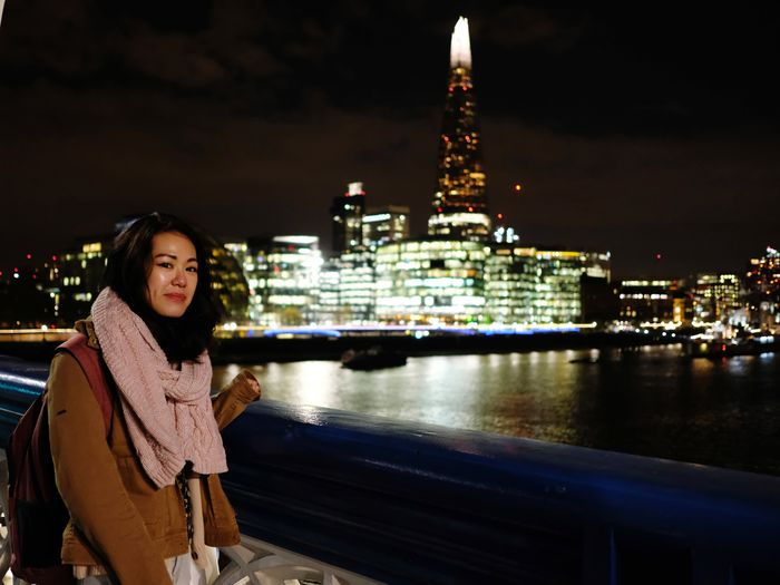 Portrait of woman standing by illuminated cityscape against sky at night