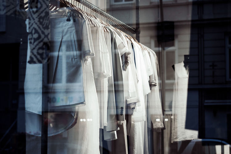 Clothes Hanging On Rack At Store Seen Throw Glass Window