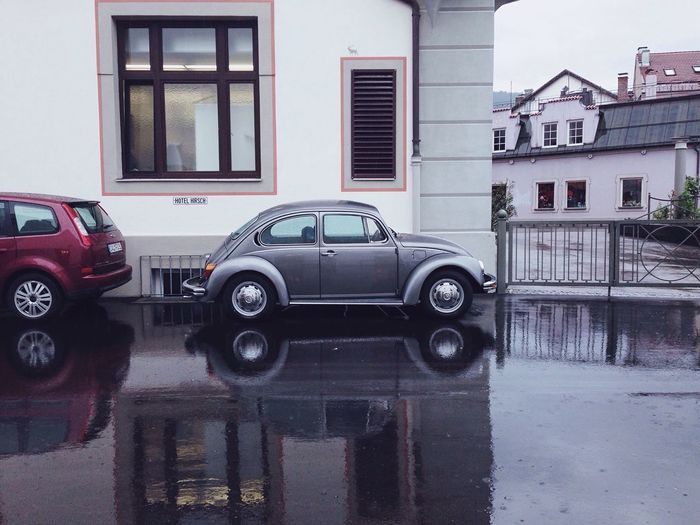 Vintage Car Parked Against Building On Wet Street In City During Rainy Season