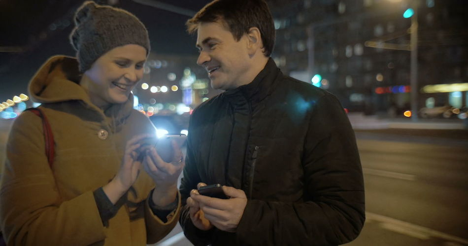Young man holding smart phone while standing in city at night