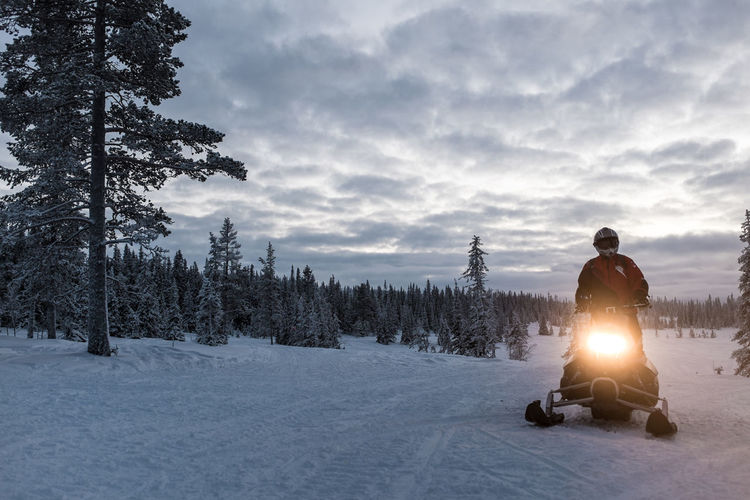 Man Riding Snowmobile On Snow Covered Landscape Against Sky