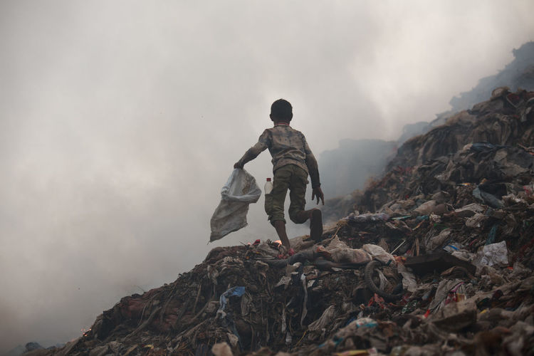 Full length of boy running on garbage dump against sky