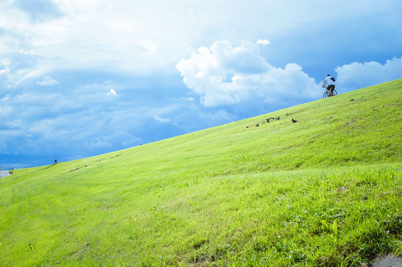 Man Riding Bicycle On Grassy Field Against Sky