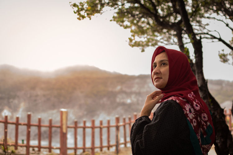 Thoughtful Woman Wearing Hijab While Standing Against Mountain