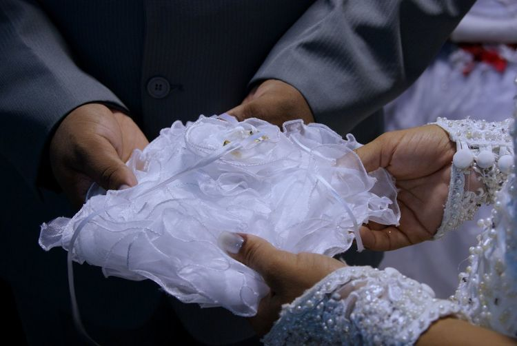 Midsection Of Bride And Bridegroom Holding White Textile During Wedding