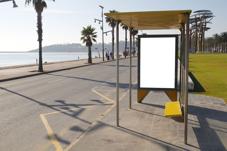 Blank billboard in a bus stop, for advertisement Ad Advertisement Advertising Banner Bannerpic Billboard Blank Bus Bus Stop Commercial Marketing Mock Up Palm Trees Palms Poster Posters Road Sea Shelter Stop Street Urban Water White