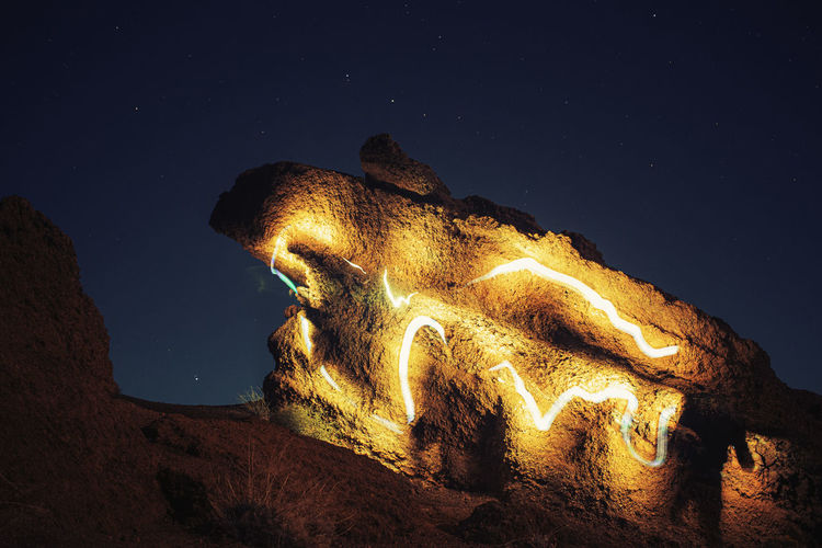 Low angle view of illuminated rock formation against sky at night