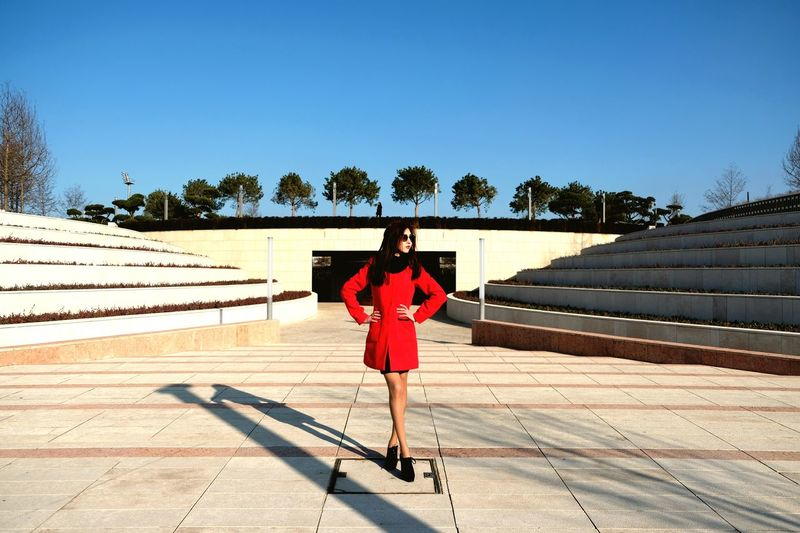 Woman standing amidst steps in city against clear blue sky