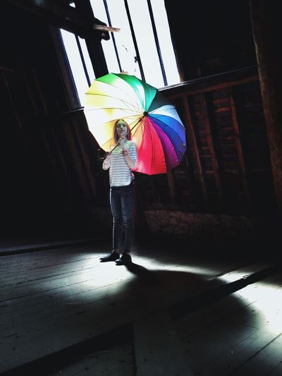 Rear view of woman standing against multi colored umbrella