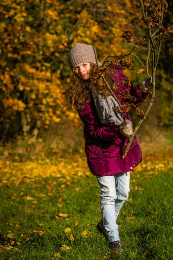 Full length of woman with autumn leaves in park