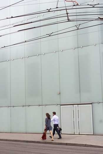Friends walking on sidewalk against building