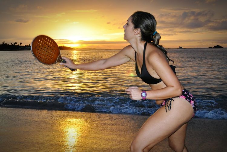 Woman in bikini playing paddle ball at beach during sunset