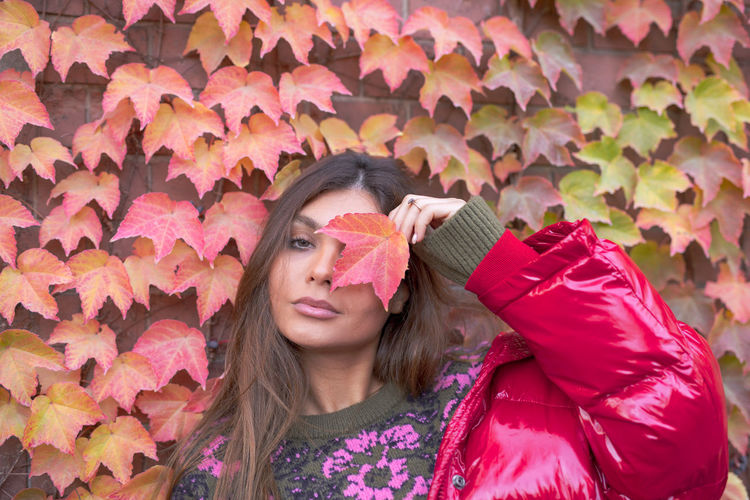 Portrait of woman with pink leaves during autumn