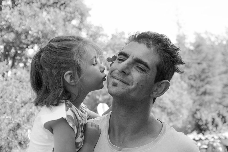 Close-up of daughter kissing father while standing outdoors